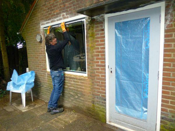 Hans en Kees plaatsen een raam, de deur zit er al in